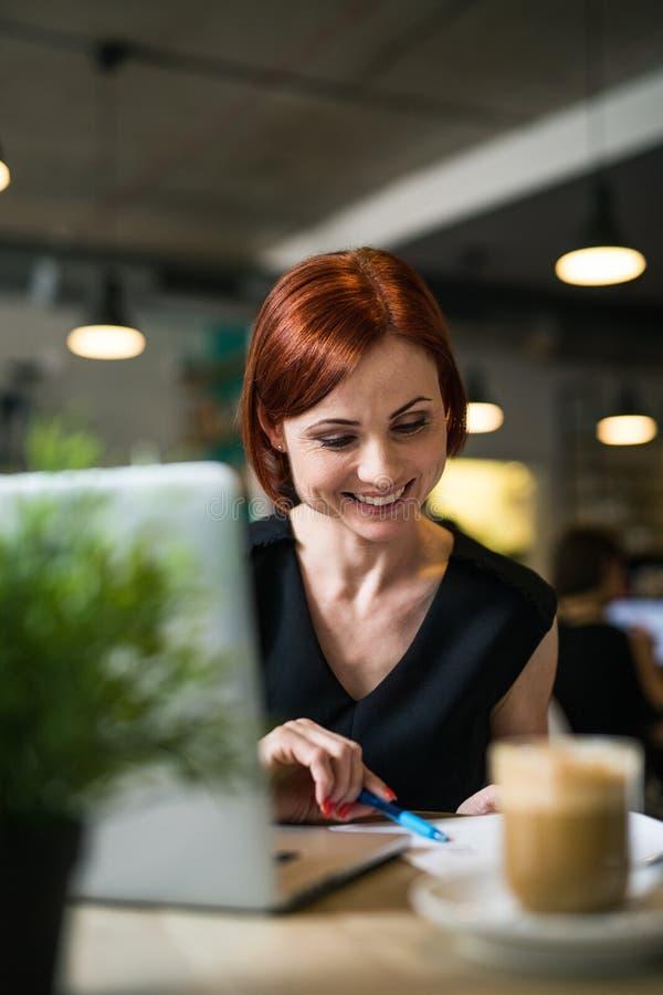 Un ritratto della donna con caffè che si siede alla tavola in un caffè, facendo uso del computer portatile immagini stock libere da diritti