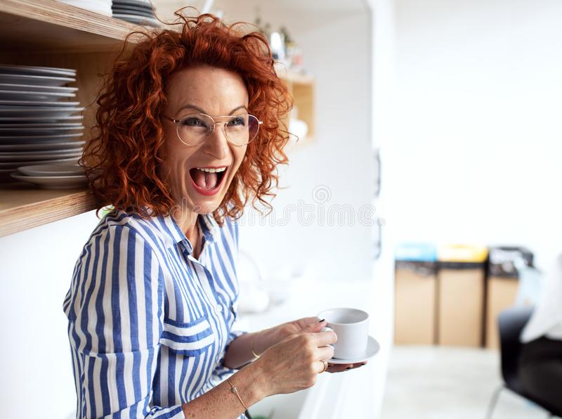 Un ritratto della donna di affari allegra in un ufficio, tenente una tazza di caffè fotografia stock