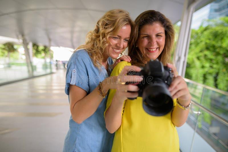 Un ritratto della donna felice due insieme all'aperto facendo uso della macchina fotografica immagini stock