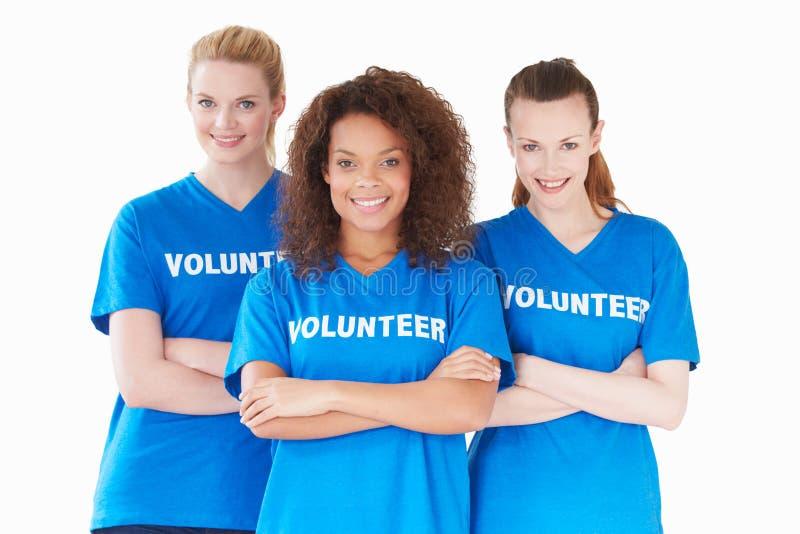 Un ritratto dello studio di tre donne che portano le magliette volontarie fotografie stock