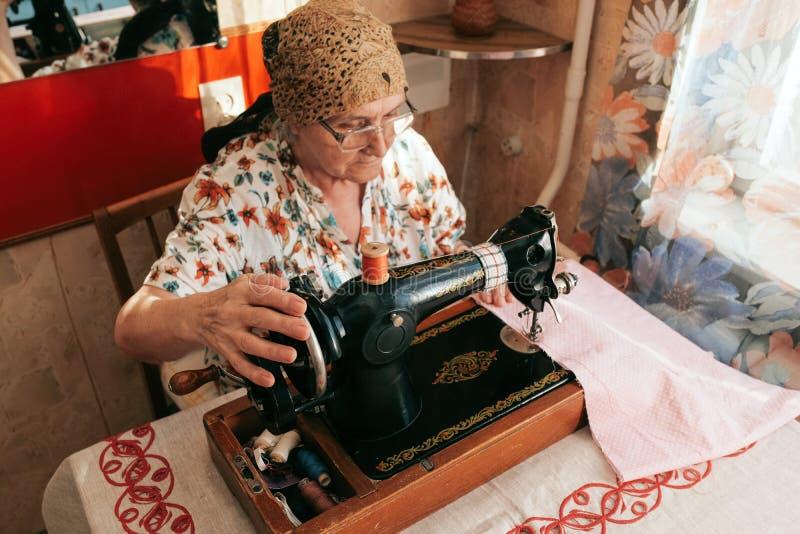 Un ritratto di 70 anni della donna senior in occhiali facendo uso della macchina per cucire, lavorante dalla casa Lavoro per la g immagini stock