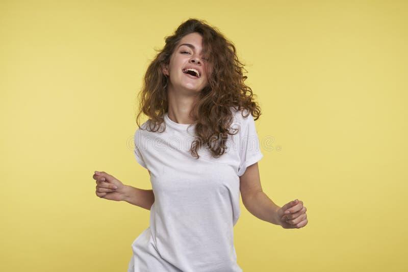 Un ritratto di ballare la giovane signora graziosa con capelli ricci castana, ha vestito casuale, contro fondo giallo fotografia stock