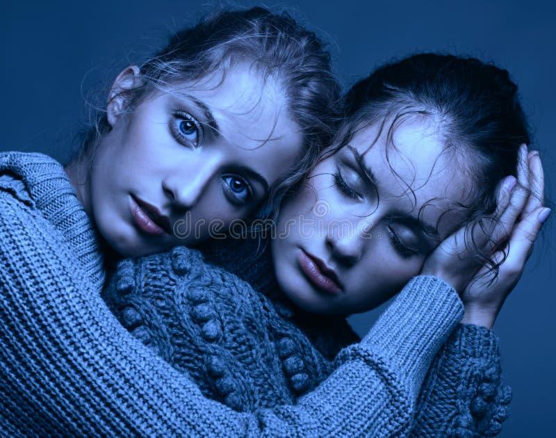 Un ritratto di bellezza di Halloween di due giovani donne in maglioni grigi sopra fotografia stock