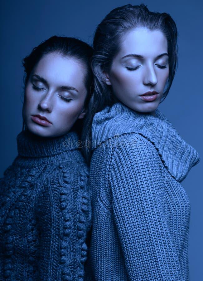 Un ritratto di bellezza di Halloween di due giovani donne in maglioni grigi sopra fotografie stock libere da diritti