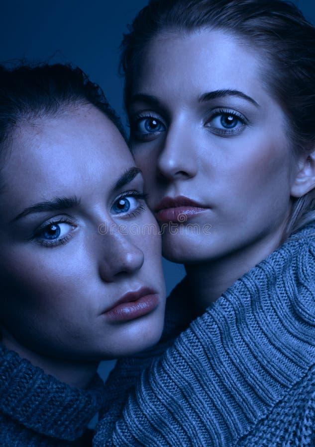 Un ritratto di bellezza di Halloween di due giovani donne in maglioni grigi sopra immagini stock