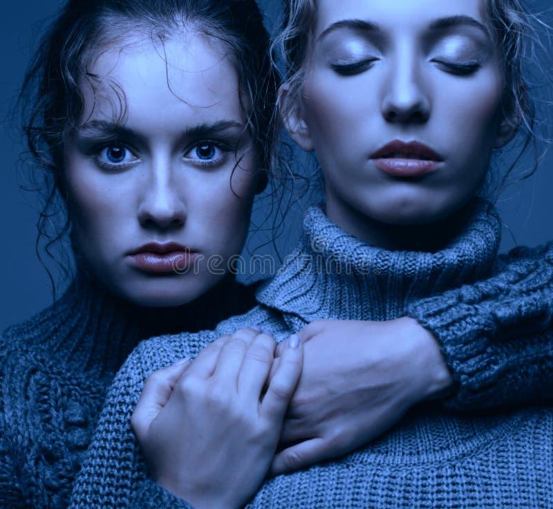 Un ritratto di bellezza di Halloween di due giovani donne in maglioni grigi sopra fotografia stock libera da diritti