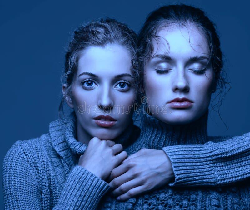 Un ritratto di bellezza di Halloween di due giovani donne in maglioni grigi sopra immagine stock
