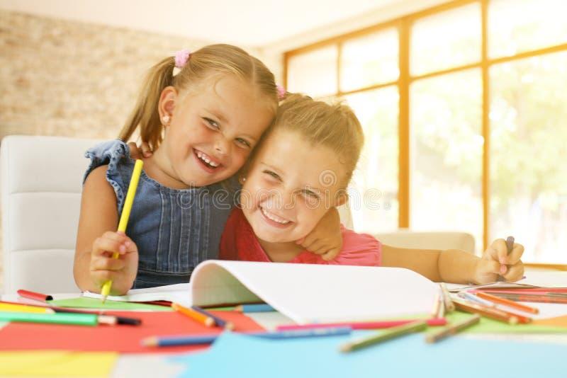 Un ritratto di un disegno e di un esame di due bambine della macchina fotografica fotografia stock