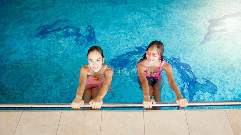 Un ritratto di due adolescenti sorridenti che nuotano nello stagno alla palestra fotografia stock