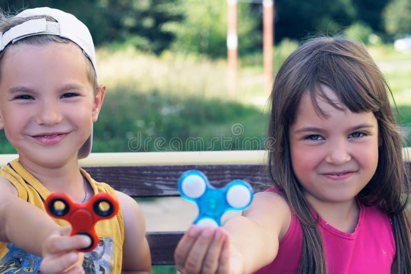 Un ritratto di due amici sorridenti divertenti che giocano con i filatori variopinti di irrequietezza sul campo da giuoco Sforzo- immagine stock