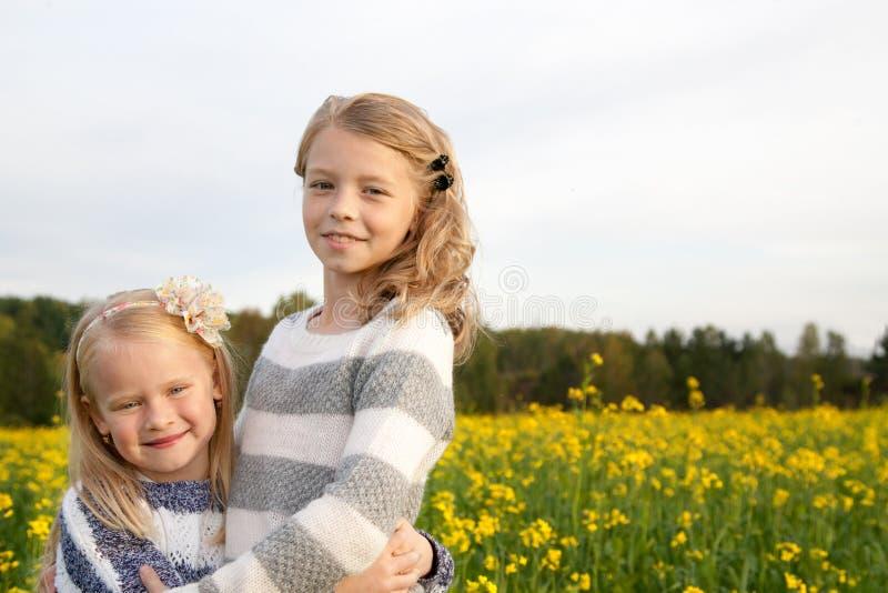 Un ritratto di due bambine sveglie d'abbraccio fotografia stock