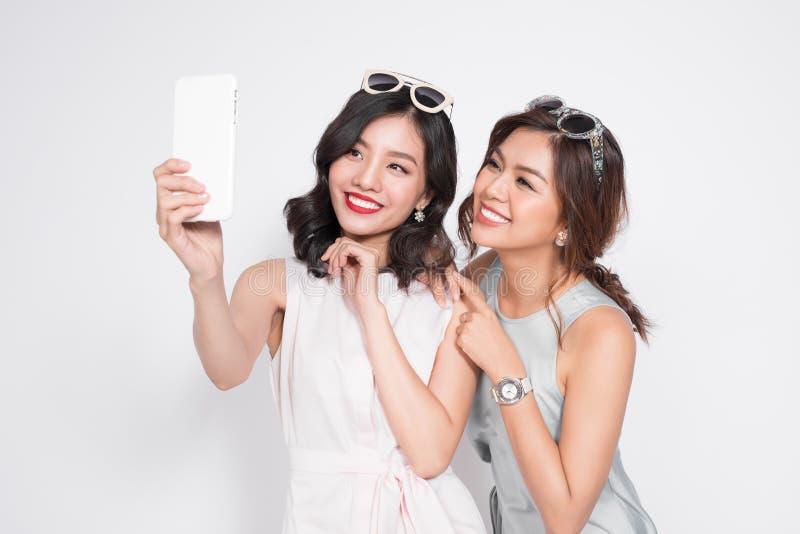 Un ritratto di due belle donne alla moda asiatiche che prendono selfie fotografia stock libera da diritti