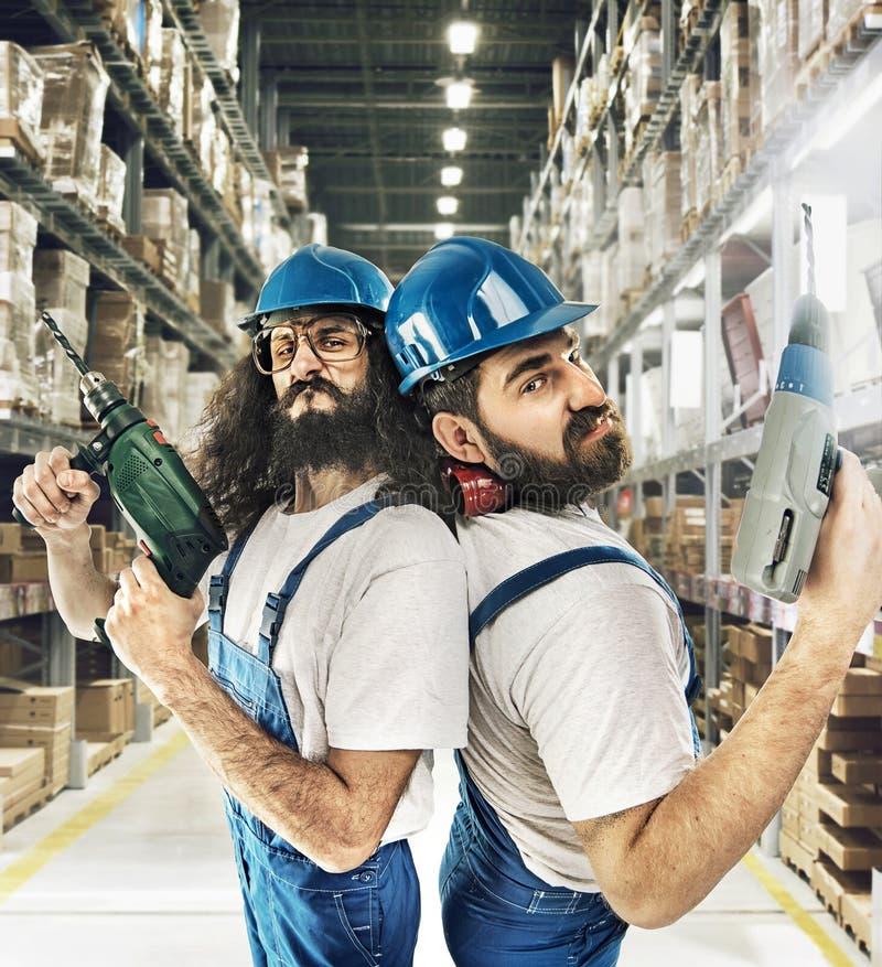Un ritratto di due costruttori in un deposito immagine stock libera da diritti