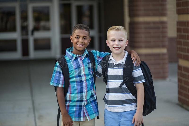 Un ritratto di due diversi bambini della scuola che stanno fuori della loro costruzione della scuola elementare fotografia stock libera da diritti