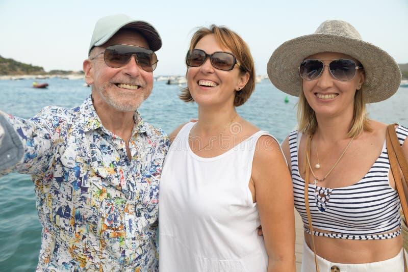 Un ritratto di due donne felici e di un uomo più anziano sopra la passeggiata della spiaggia che prende selfie fotografie stock