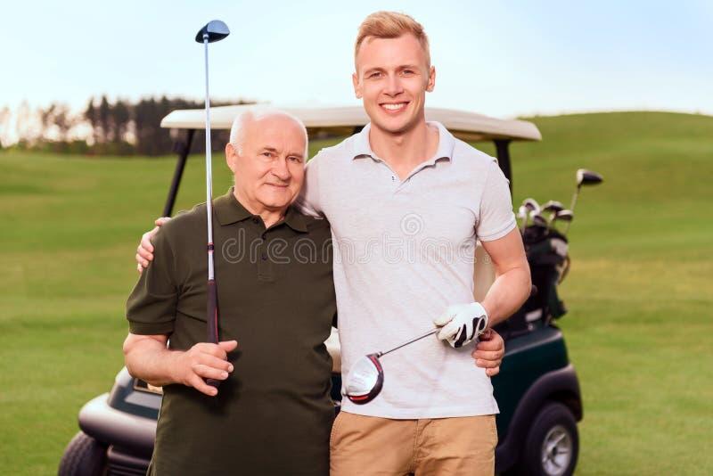 Un ritratto di due giocatori di golf sul fondo del carretto immagine stock libera da diritti