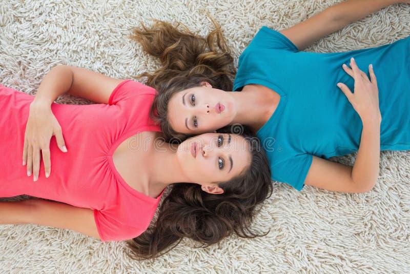 Un ritratto di due giovani amici femminili che si trovano sulla coperta fotografie stock