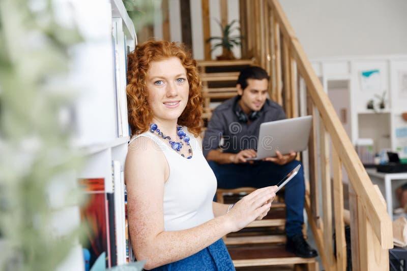 Un ritratto di due giovani che si siedono alle scale in ufficio immagini stock libere da diritti