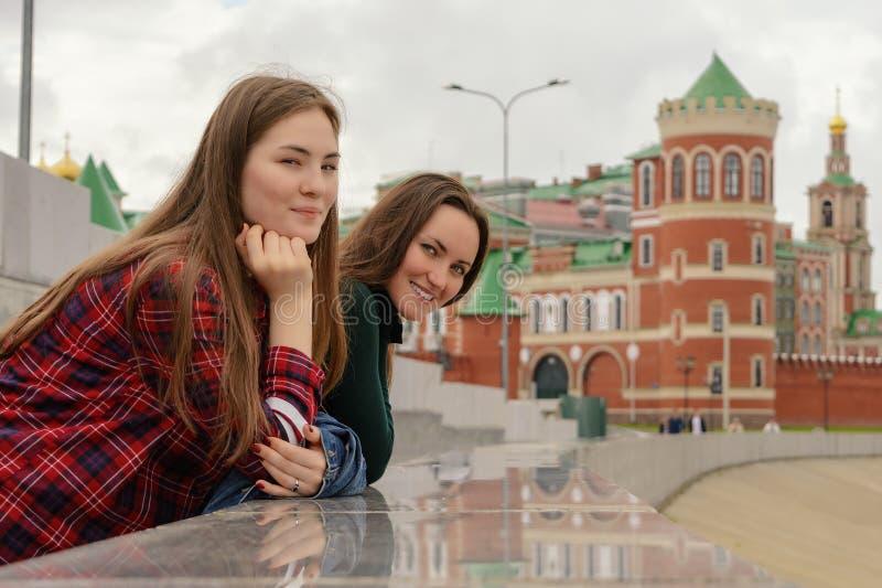 Un ritratto di due giovani donne nell'abbigliamento casual su una passeggiata intorno alla città, alla condizione e ad esaminare  immagine stock
