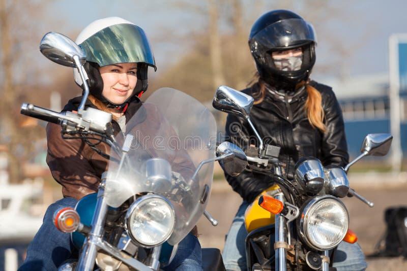 Un ritratto di due motociclisti abbastanza femminili dell'europeo con le bici di stile della via e del classico fotografia stock libera da diritti