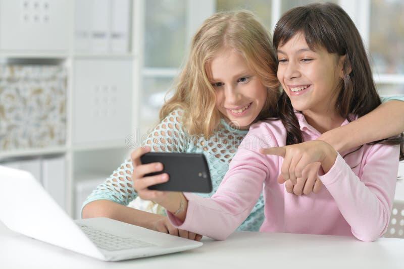 Un ritratto di due ragazze con il telefono ed il computer portatile fotografie stock libere da diritti