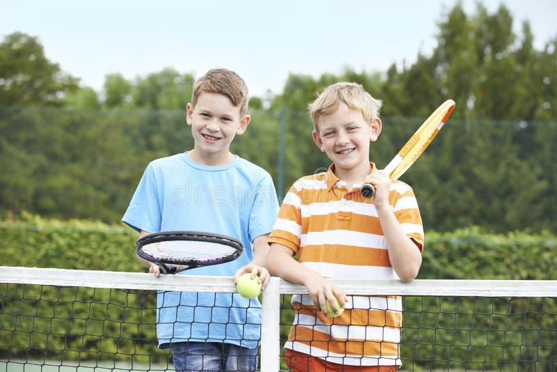 Un ritratto di due ragazzi che giocano a tennis insieme immagini stock