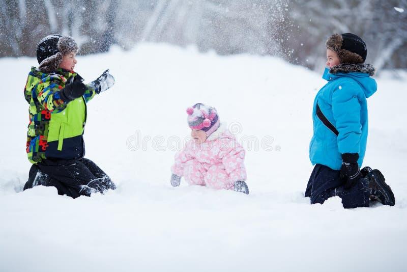 Un ritratto di due ragazzi felici allegri e la neonata nell'inverno parcheggiano fotografie stock