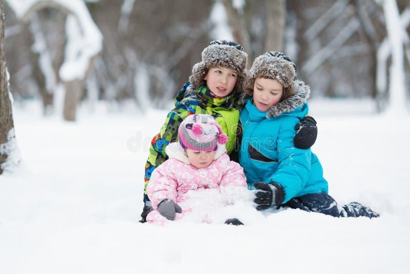 Un ritratto di due ragazzi felici allegri e la neonata nell'inverno parcheggiano fotografie stock libere da diritti