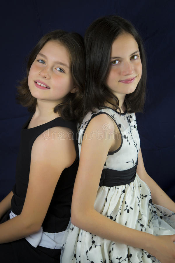 Un ritratto di due sorelle sveglie di nuovo alla parte posteriore fotografia stock libera da diritti