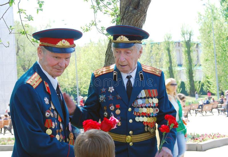 Un ritratto di due veterani di guerra che tengono i garofani rossi fotografie stock libere da diritti