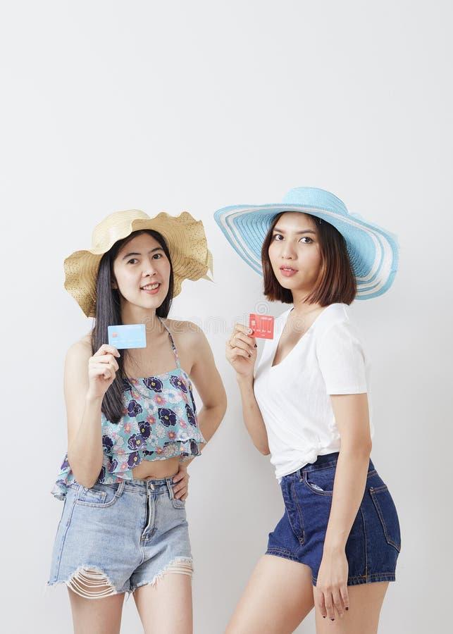 un ritratto di un fondo bianco di due ragazze dei pantaloni a vita bassa fotografia stock