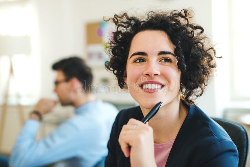 Un ritratto di giovane donna di affari con i colleghi in un ufficio moderno immagine stock libera da diritti