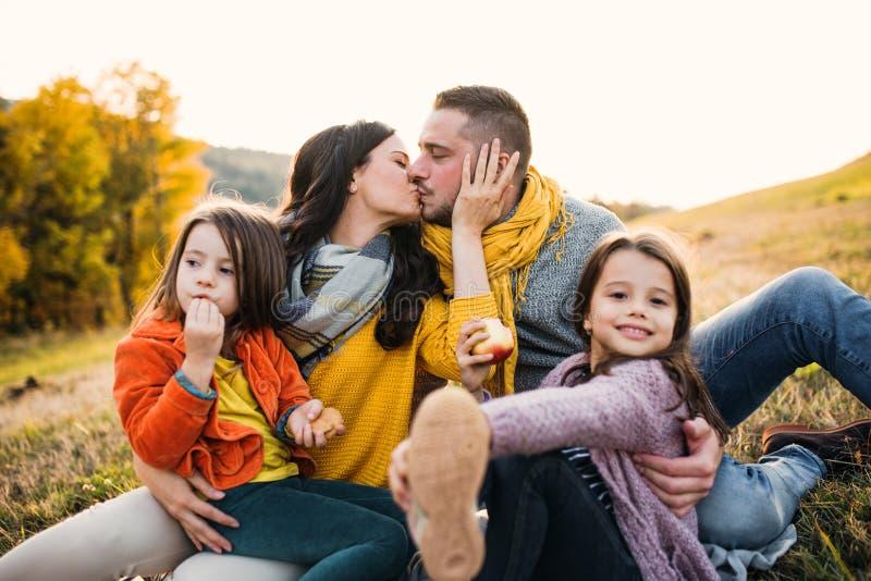 Un ritratto di giovane famiglia con due piccoli bambini in natura di autunno al tramonto, baciante immagini stock