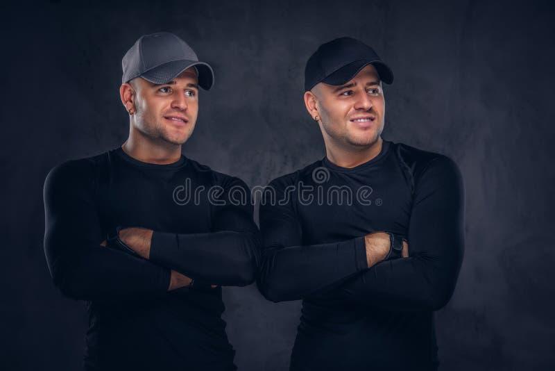 Un ritratto di giovane maschio bello due si è vestito in uno sportswea nero immagine stock