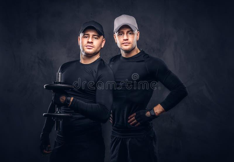 Un ritratto di giovane maschio bello due si è vestito in uno sportswea nero immagini stock libere da diritti