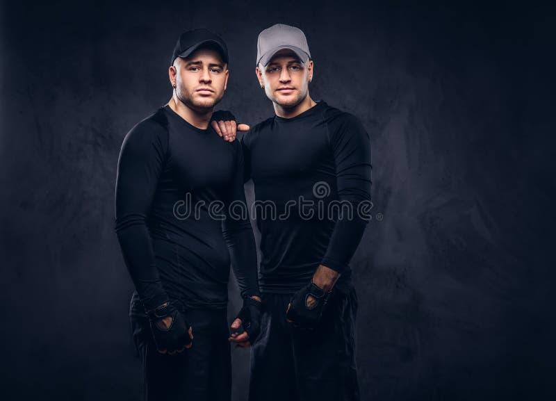 Un ritratto di giovane maschio bello due si è vestito in uno sportswea nero immagine stock libera da diritti