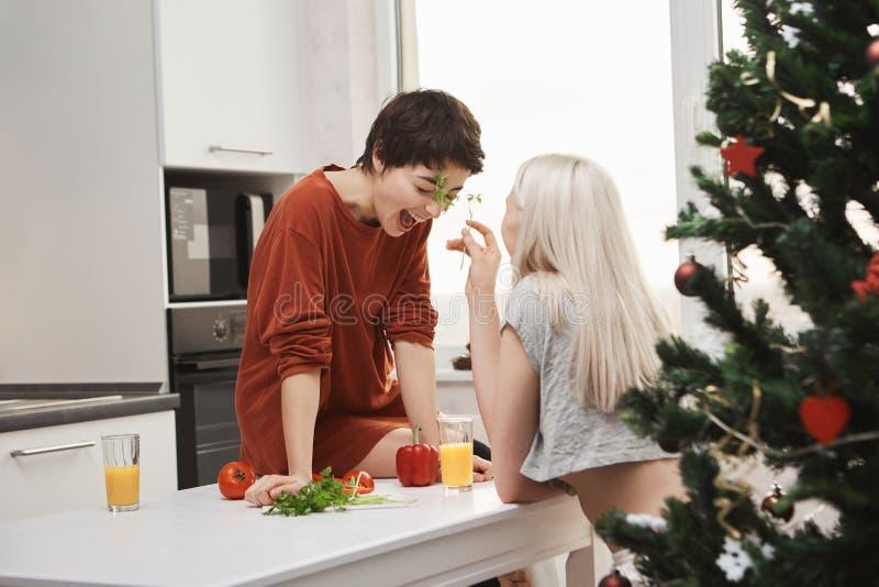 un ritratto di Laterale vista di due ragazze che ridono e che si divertono nella cucina, mentre preparando insalata il giorno dop immagini stock libere da diritti