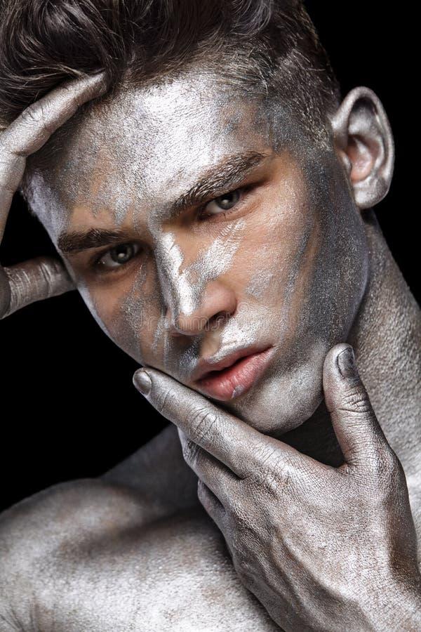 Un ritratto di modo dell'uomo con arte d'argento del fronte e del bodyart fotografie stock libere da diritti