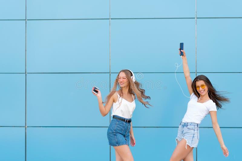 Un ritratto di modo di una donna sorridente graziosa di due pantaloni a vita bassa in occhiali da sole che tengono smartphone e c fotografia stock libera da diritti