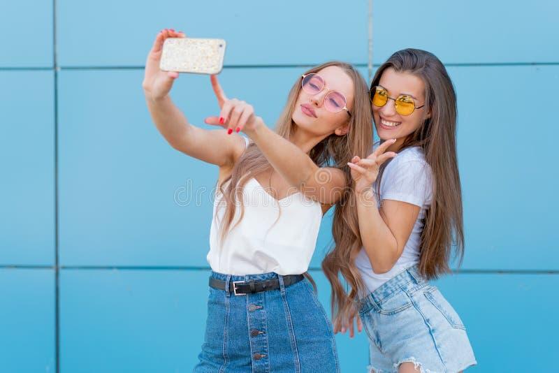 Un ritratto di modo di una donna sorridente graziosa di due pantaloni a vita bassa in occhiali da sole che tengono smartphone e c fotografie stock
