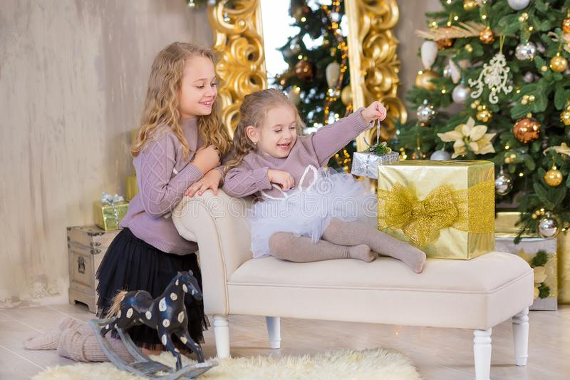 Un ritratto di Natale di due amici sorridenti delle sorelle delle ragazze sveglie beautyful e dell'albero bianco verde di lusso d immagine stock libera da diritti