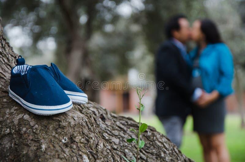Un ritratto di un paio delle scarpe di bambino con una donna incinta ed il suo marito nei precedenti fotografia stock