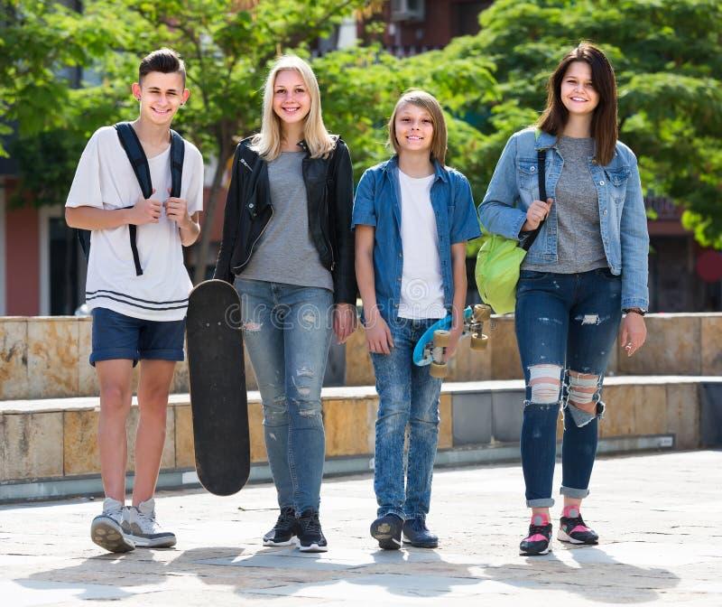 Un ritratto di quattro adolescenti che camminano insieme nella città su estate da immagine stock