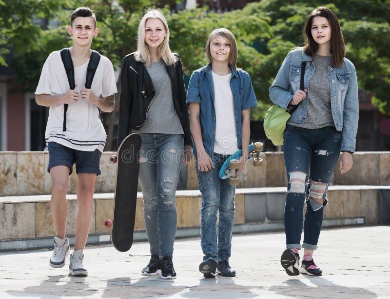 Un ritratto di quattro adolescenti che camminano insieme nella città su estate da immagini stock