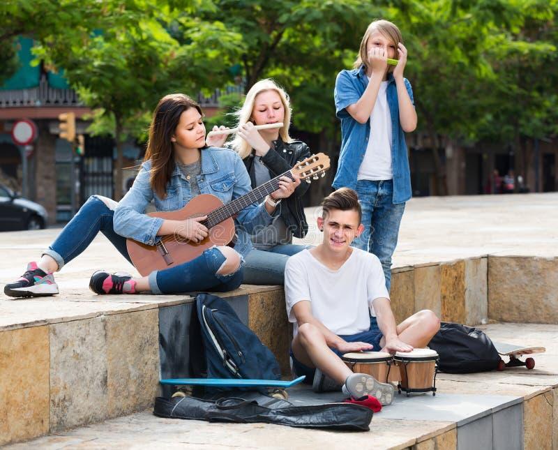Un ritratto di quattro adolescenti che giocano insieme musica all'aperto fotografia stock
