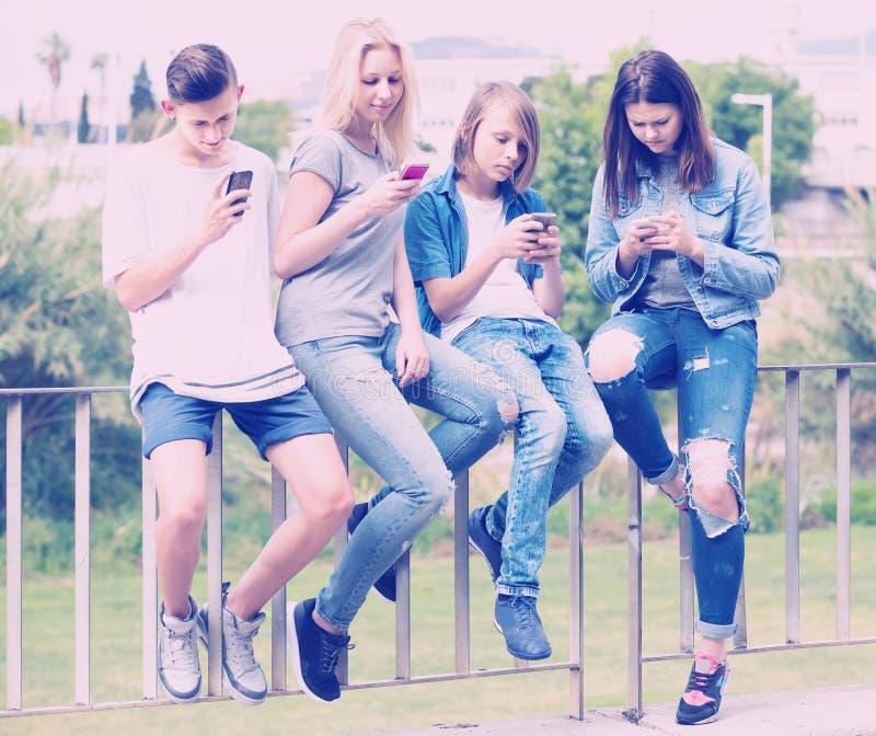 Un ritratto di quattro adolescenti che si siedono con il loro outd dei telefoni cellulari immagine stock
