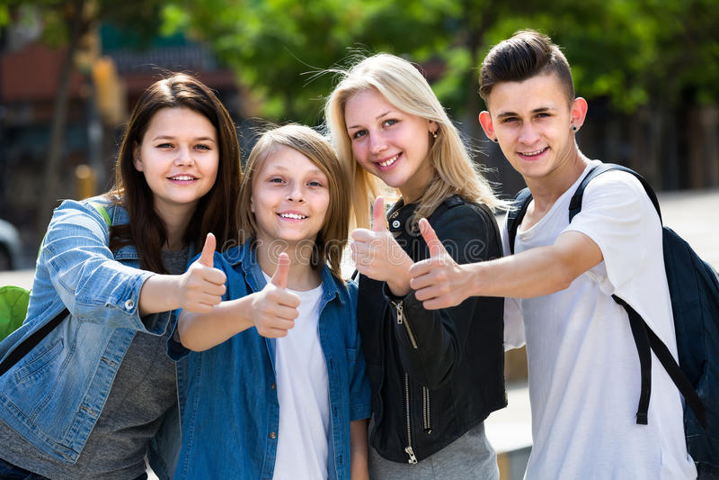 Un ritratto di quattro adolescenti che stanno e che tengono sfoglia su togeth fotografie stock