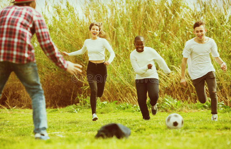 Un ritratto di quattro amici che posano sul campo della campagna con la palla fotografie stock