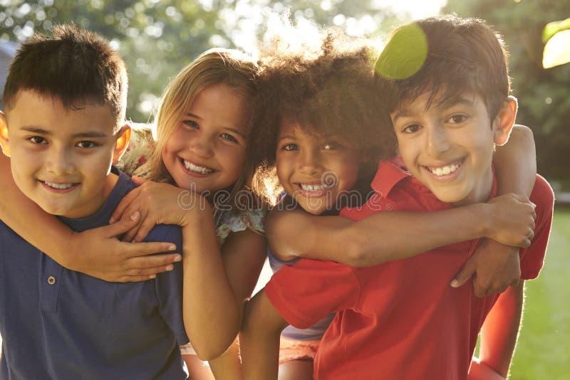 Un ritratto di quattro bambini divertendosi all'aperto insieme fotografie stock