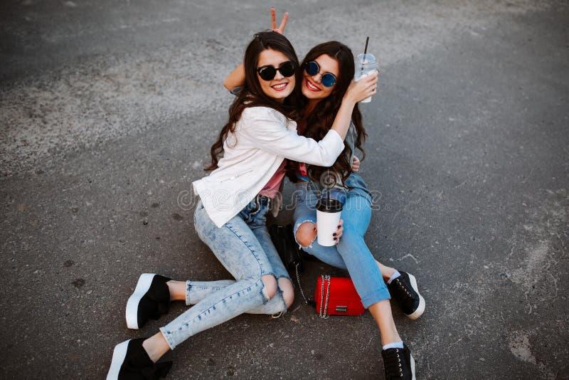 Un ritratto di stile di vita di estate di due donne alla moda dei pantaloni a vita bassa con l'ente sexy di misura, l'attrezzatur fotografia stock
